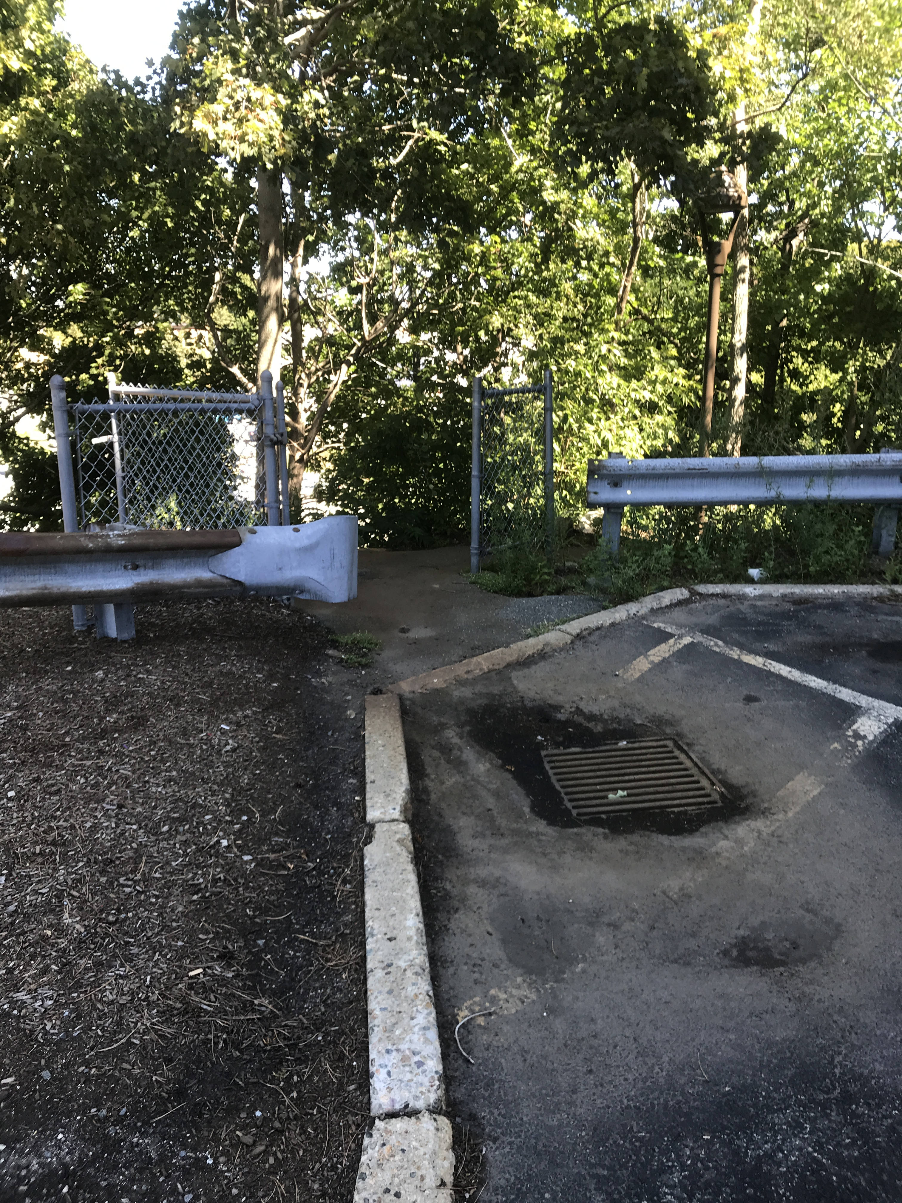 A small break between two guard rails reveals two freestanding sections of fence with an open gate between them. In front of the opening is a storm drain with a muddy puddle drying around it.