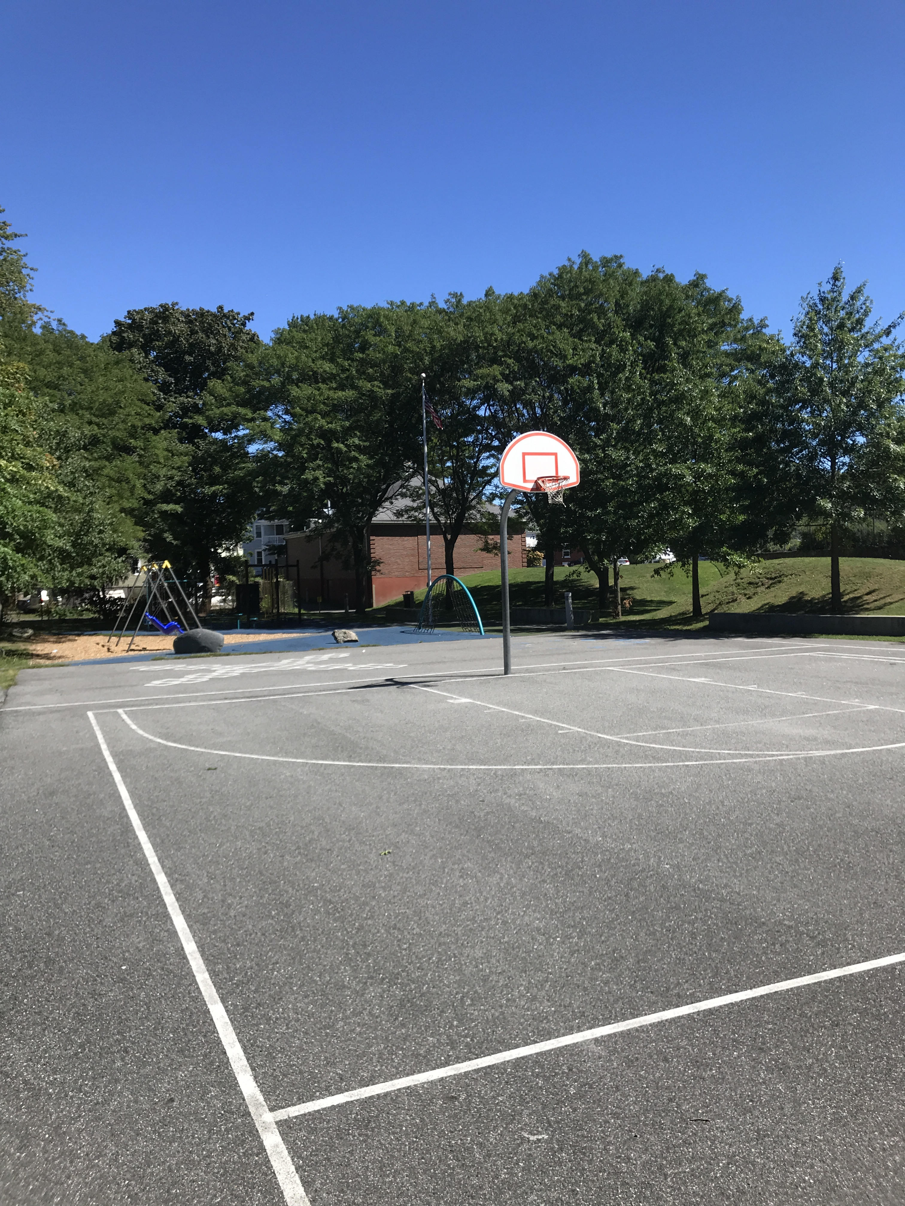 A view across a basketball court, with playground equipment in the background.