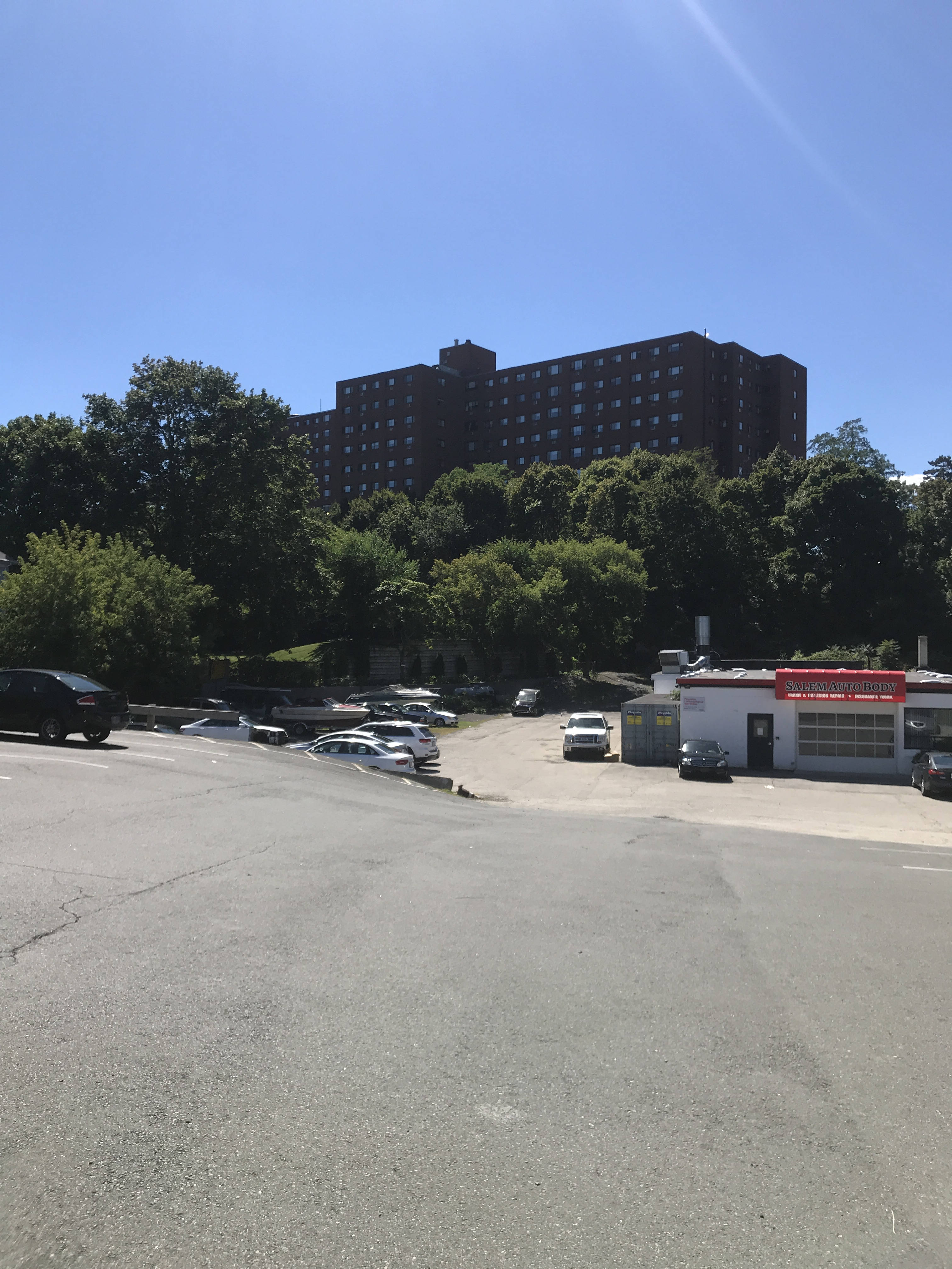 A view across a street. In the middle ground is an auto-body shop surrounded by a sizeable lot with a few cars parked in it. Behind the lot is a wooded area, and behind that, six stories of a long dark brick building rise over the trees.