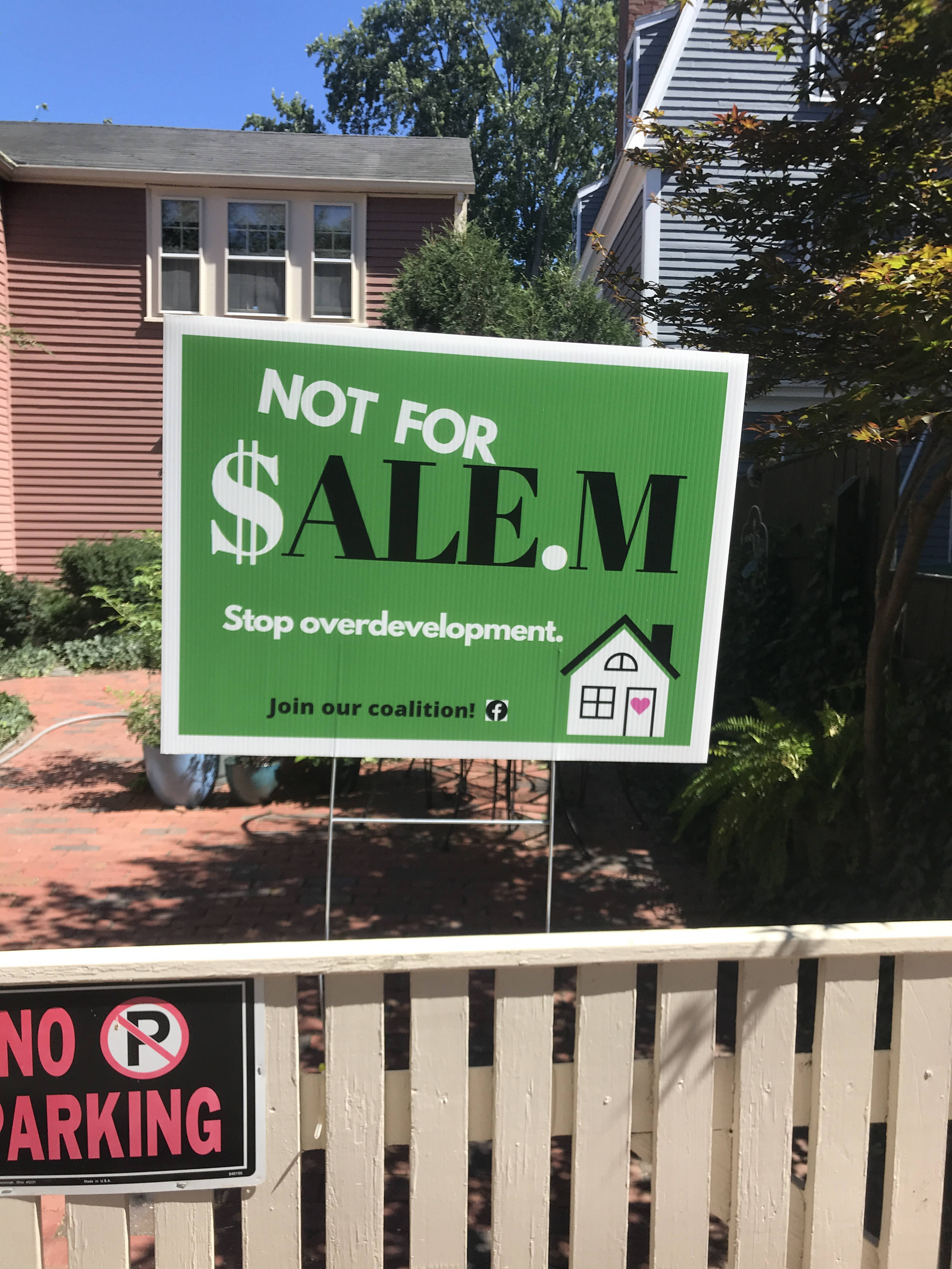 A cream-colored fence in front of an antique home. The fence bears a 'No Parking' sign and one of the 'Not For $alem' signs. The 'Not for $alem' sign says 'Stop Overdevelopment. Join our coalition!' and has a picture of a single-family house on it. The door of the house is decorated with a heart.