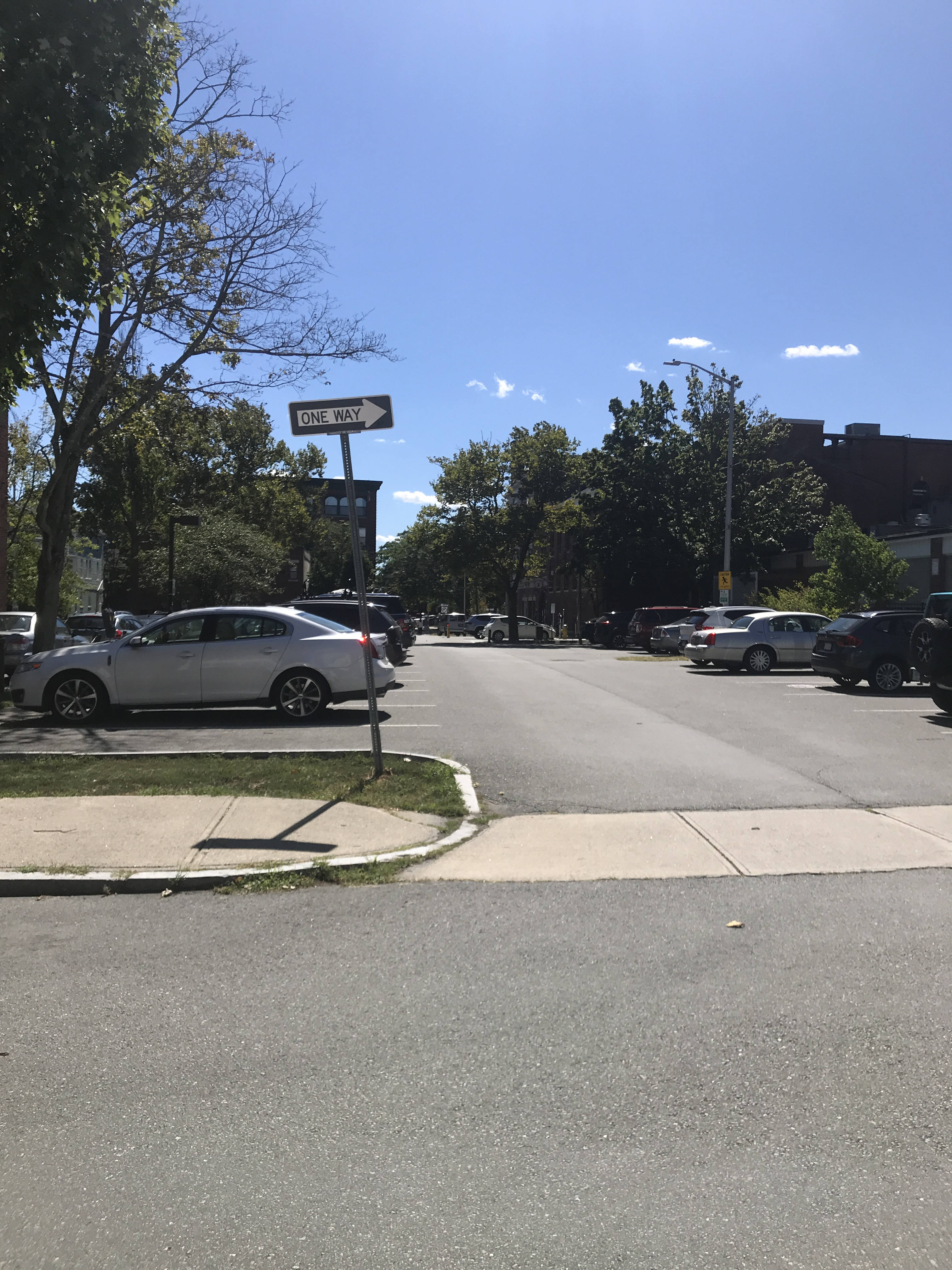 A view from one side of a street, across the street, where a parking lot also serves as a cross-street to the next street over