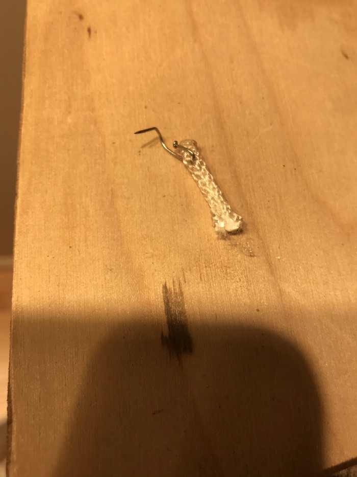 bent dressmaker's pin used as a staple in the end of a piece of paracord